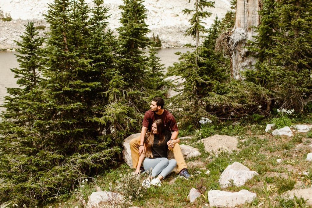 couple sitting together in the forest in Wyoming while having their engagement photos taken