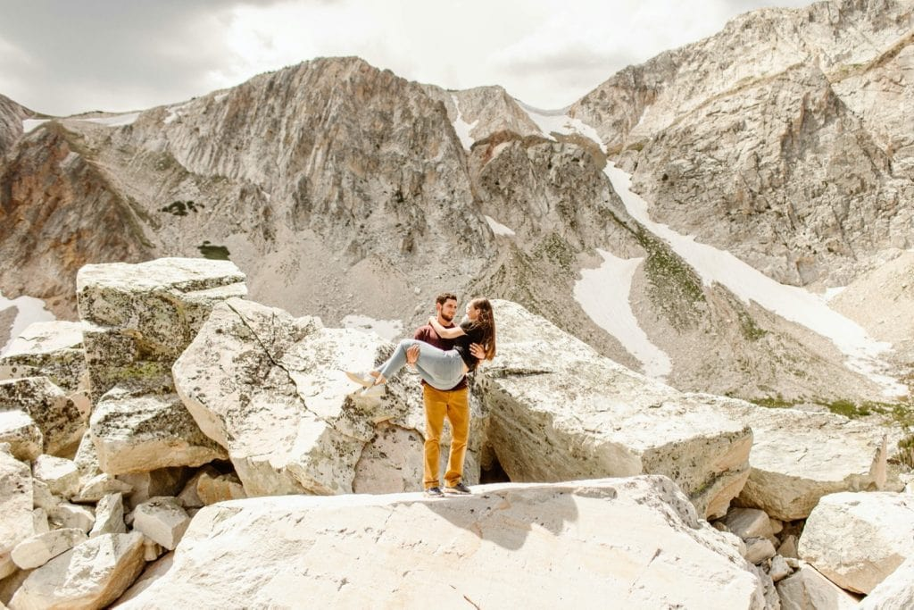 guy carrying girl through a boulder field on a mountaintop during their engagement session in Wyoming