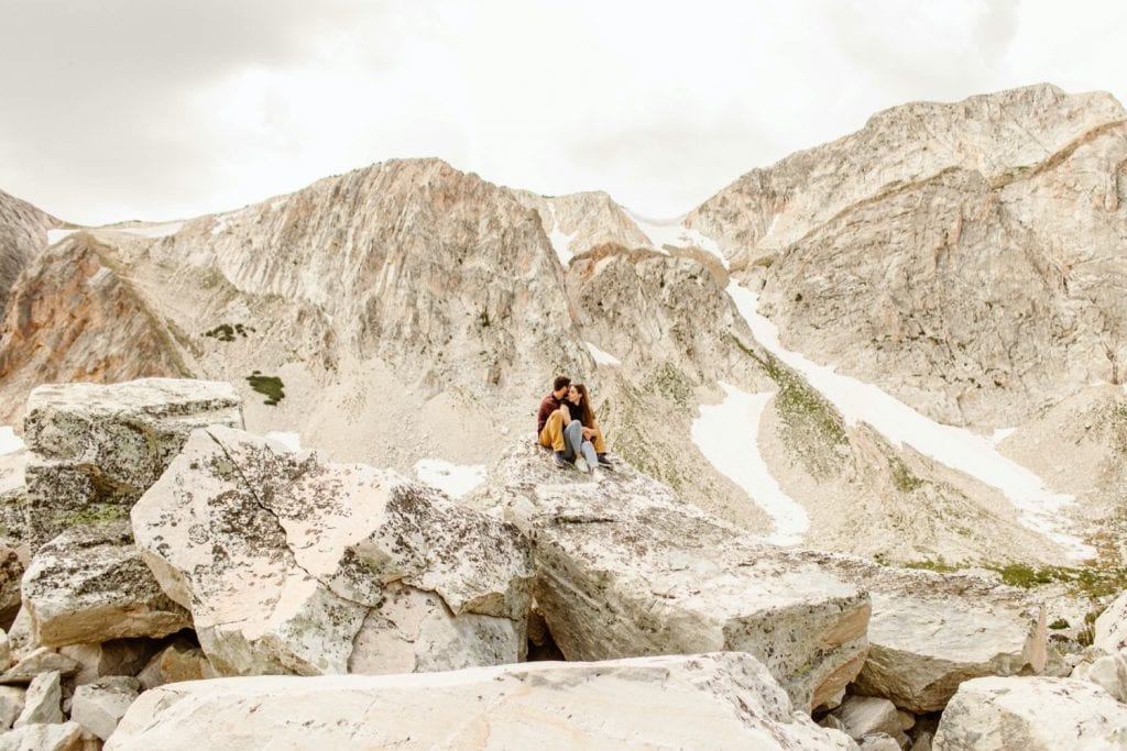 engaged couple sitting on a rocky mountain top during their mountain engagement photos in Wyoming