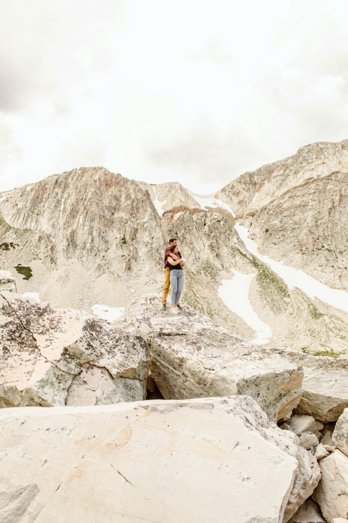 engaged couple standing on the top of a mountain in Wyoming