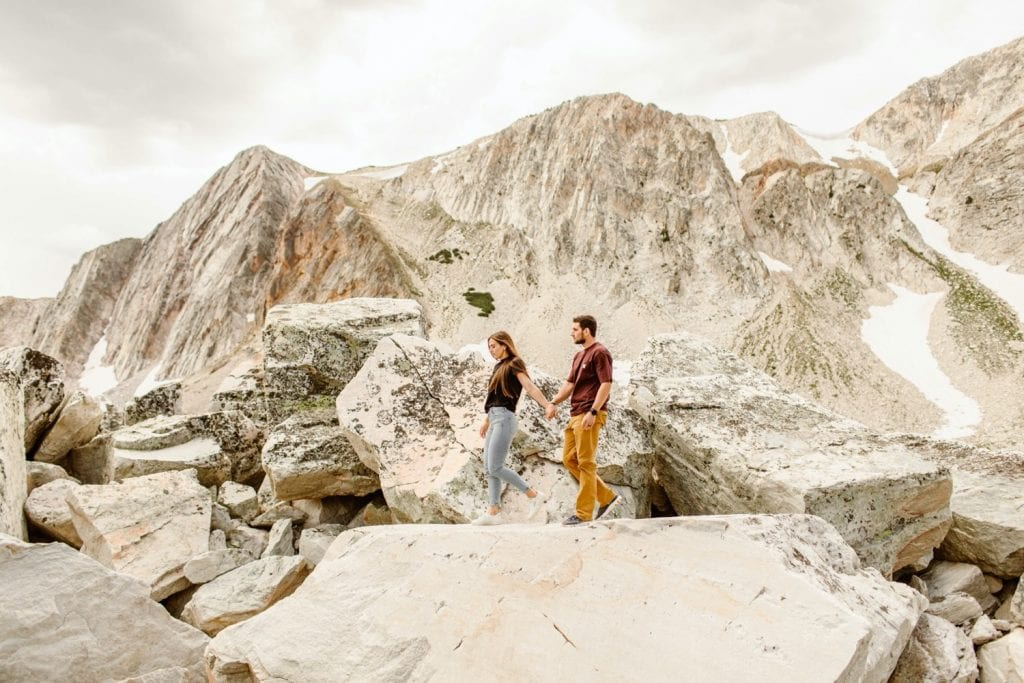engaged couple hiking down the mountain during their mountain engagement photos
