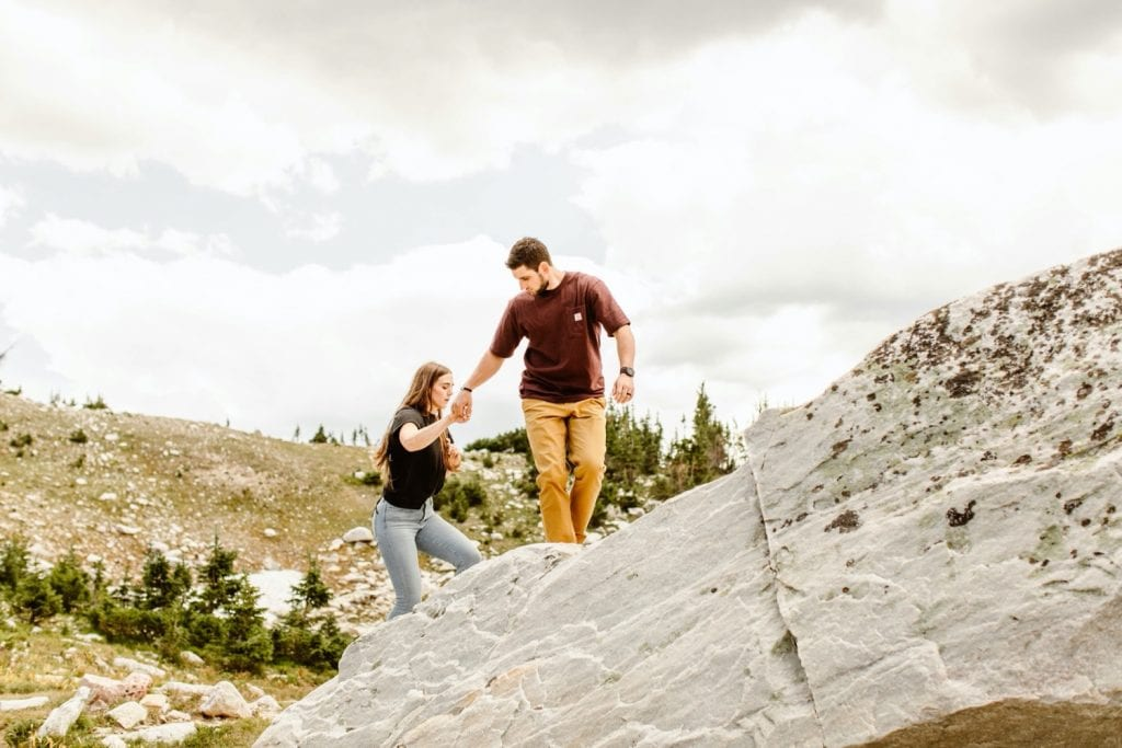 engaged couple hiking up the mountain during their mountain engagement photos