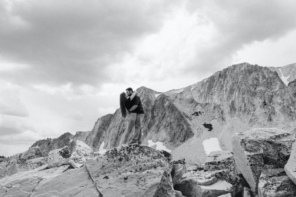 engaged couple kissing on a mountaintop in Wyoming