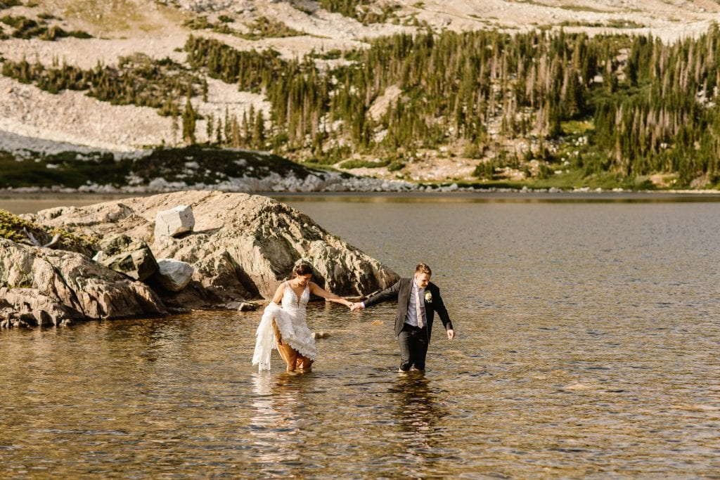 Wyoming wedding couple wading in the water after their ceremony
