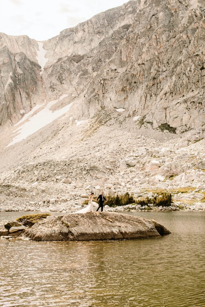 Wyoming wedding couple running on an island in an alpine lake