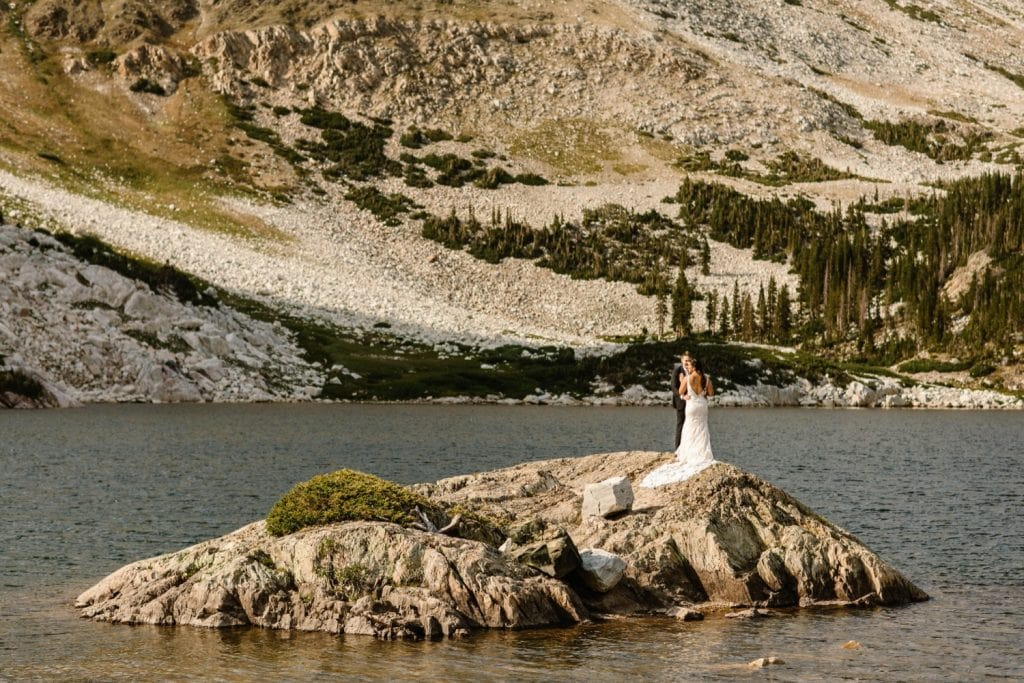 Wyoming wedding couple standing on an island in an alpine lake