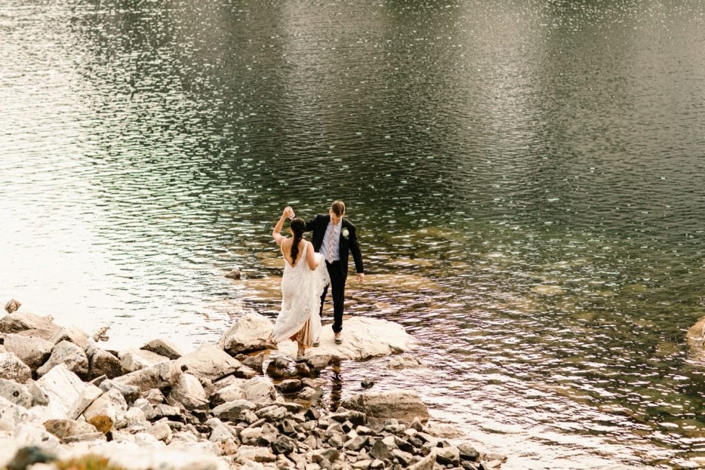 groom helping bride onto a rock by a lake