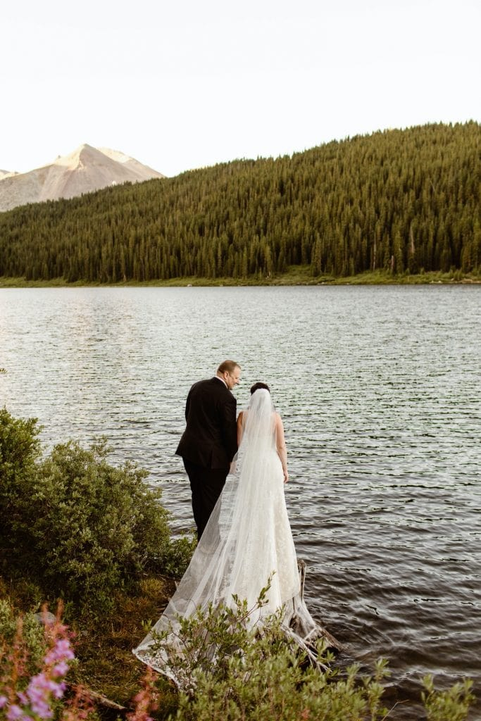 destination elopement couple standing by the lake and admiring the mountain view