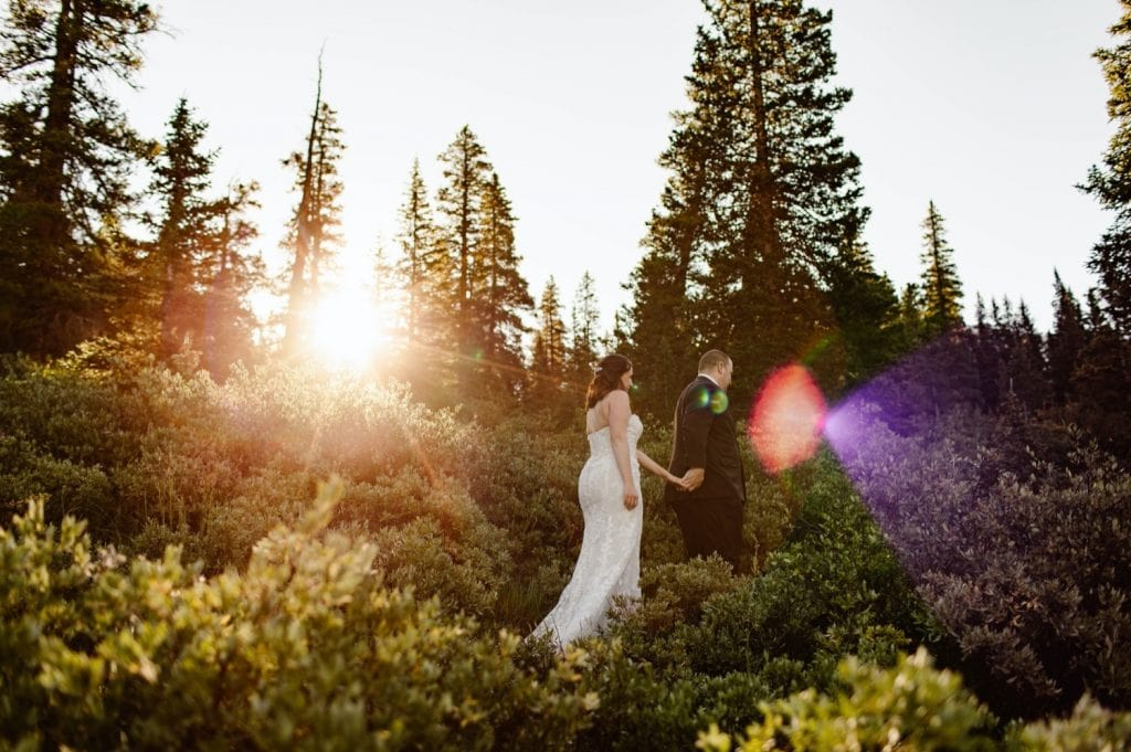couple walking down a trail at sunrise after their elopement ceremony