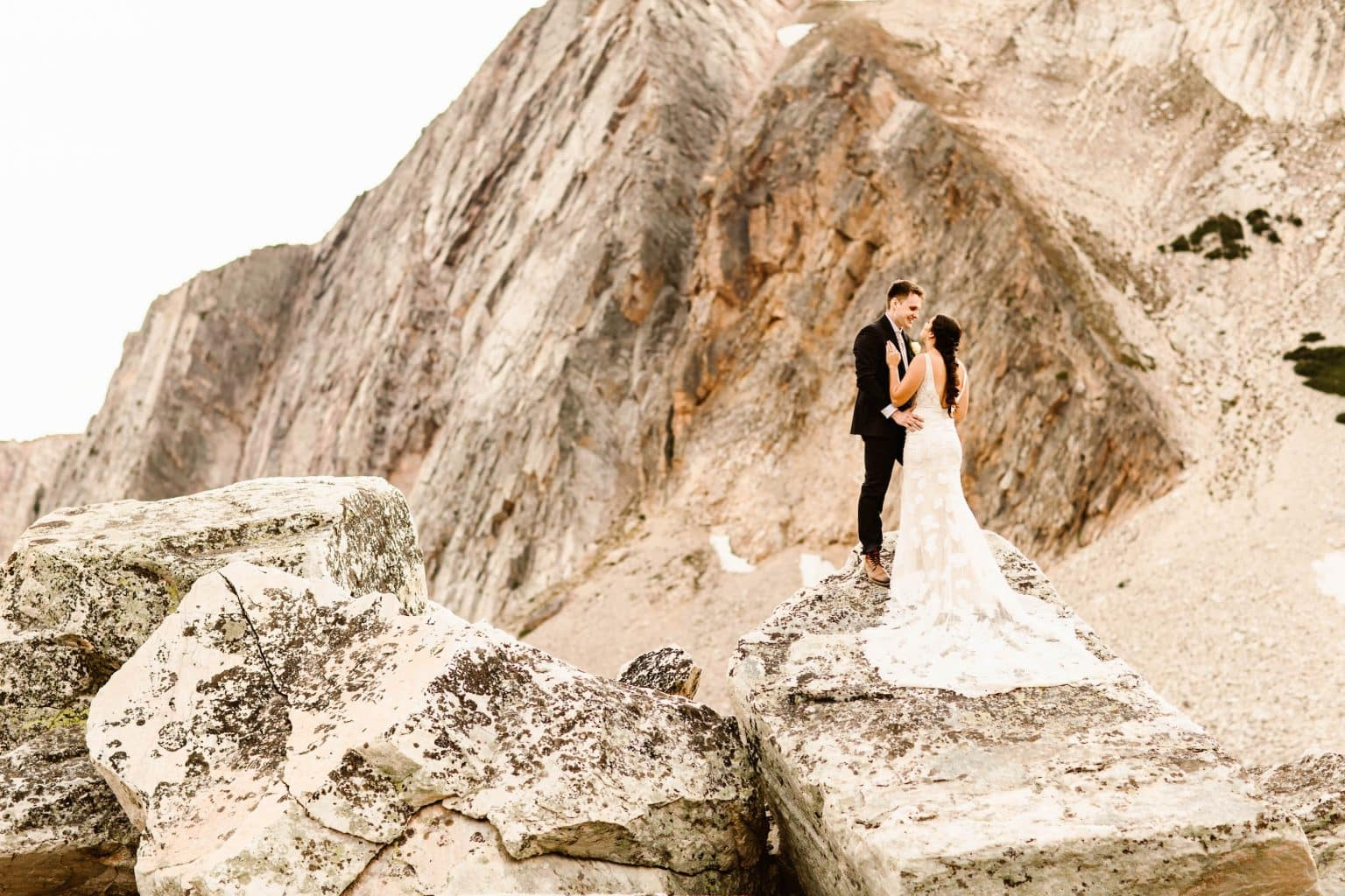 elopement advice | couple standing on a rocky granite mountain on their elopement day