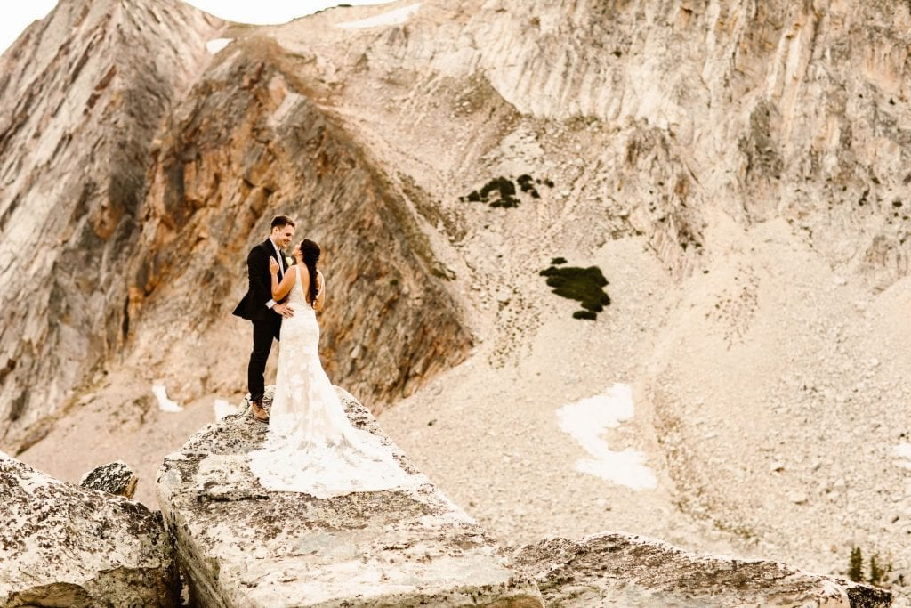 couple climbing in the mountains in their adventure wedding attire photographed by Colorado elopement photographers