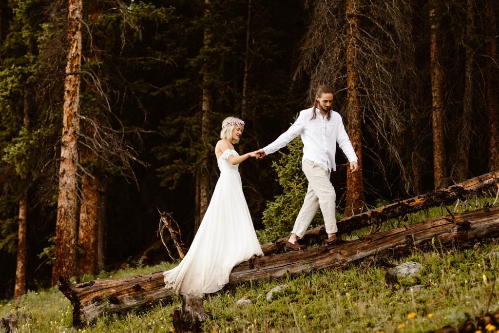 how much does it cost to elope | eloping couple walking on a fallen tree trunk