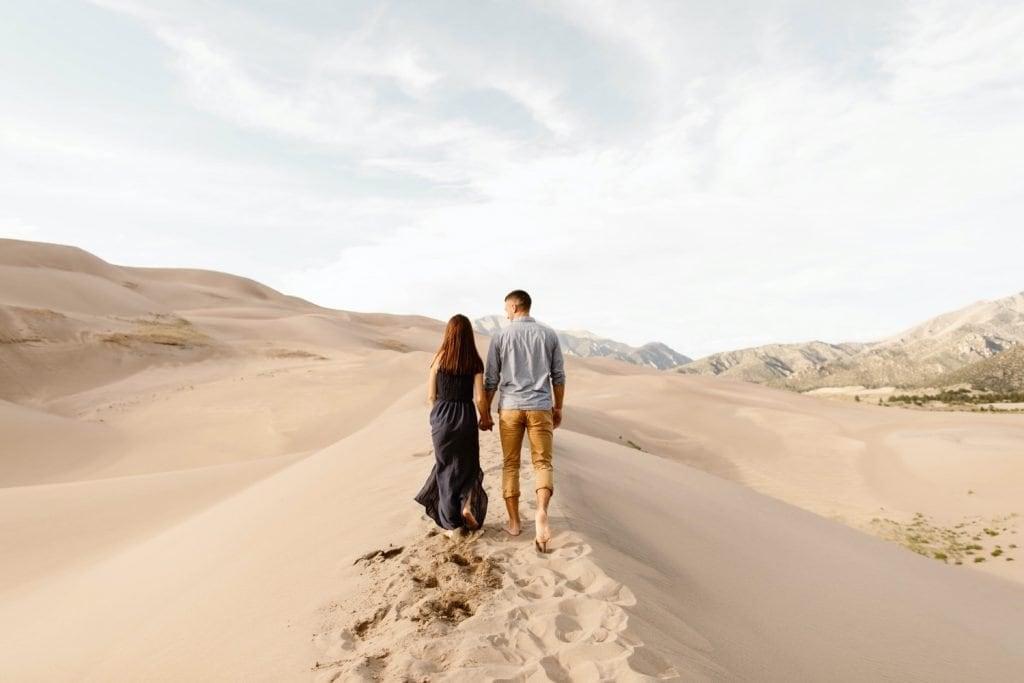 sand dunes engagement photos of a couple walking on the dune ridge