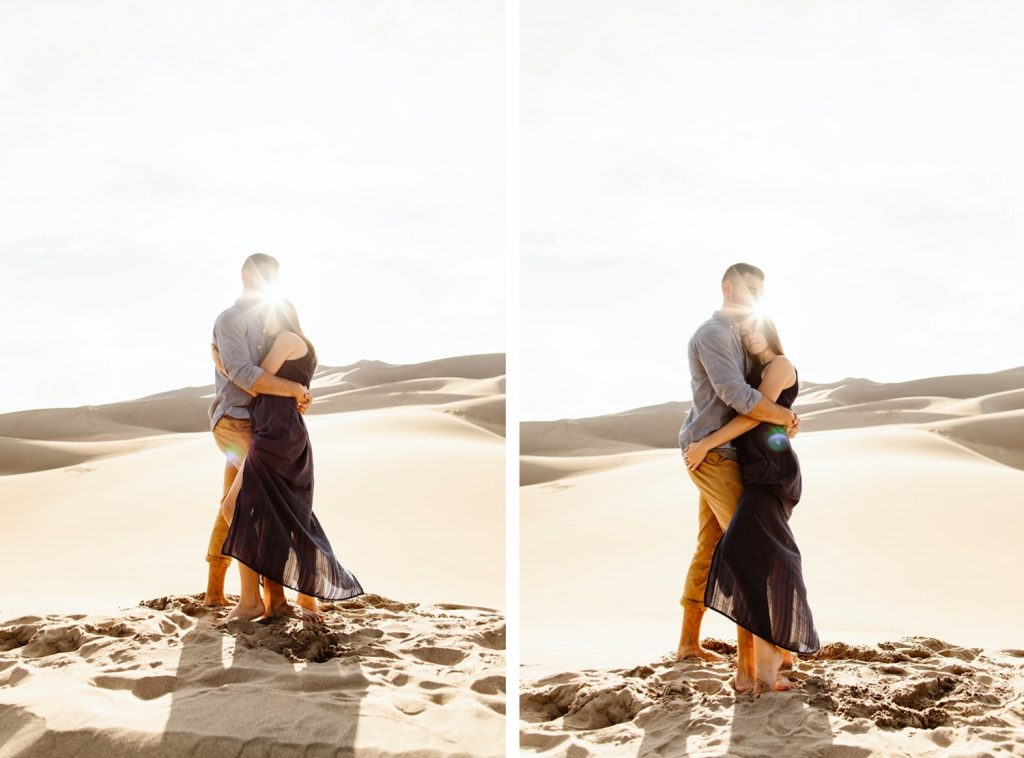 sand dunes engagement photos of a couple hugging with the sun shining between them