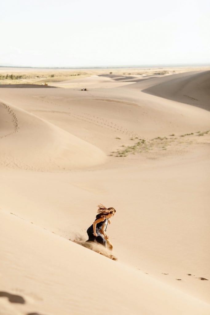 couple running down the giant dune field during their sand dunes engagement photos