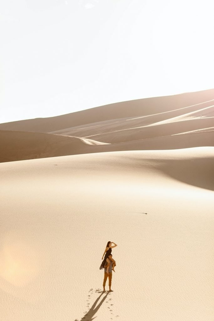girl sitting on guy's shoulders at the sand dunes
