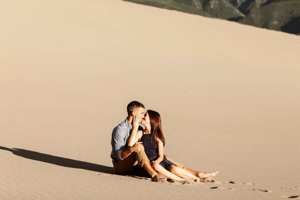 engaged couple snuggling up on the sand during their sand dunes engagement photos