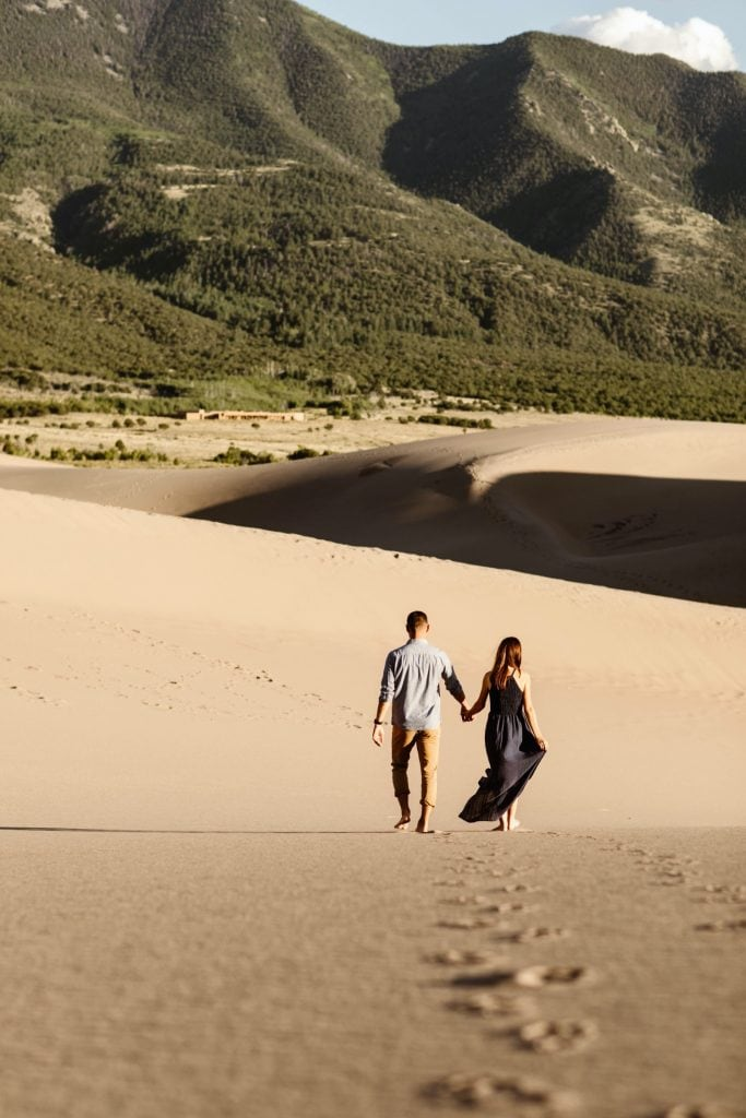 couple walking across the giant dune field during their sand dunes session