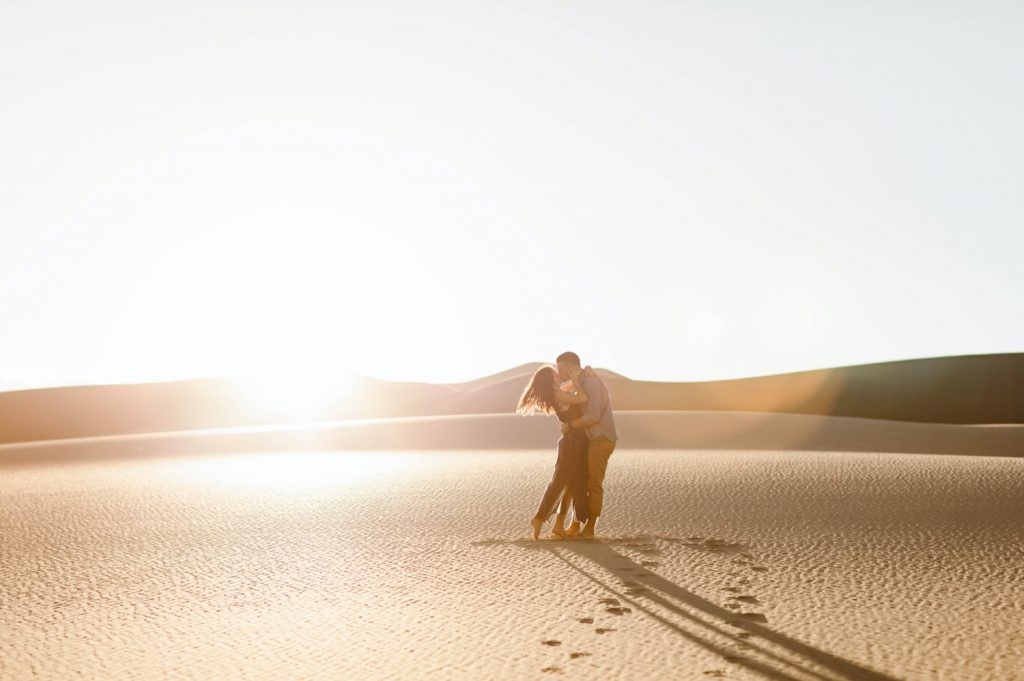 couple kissing at sunset at the sand dunes