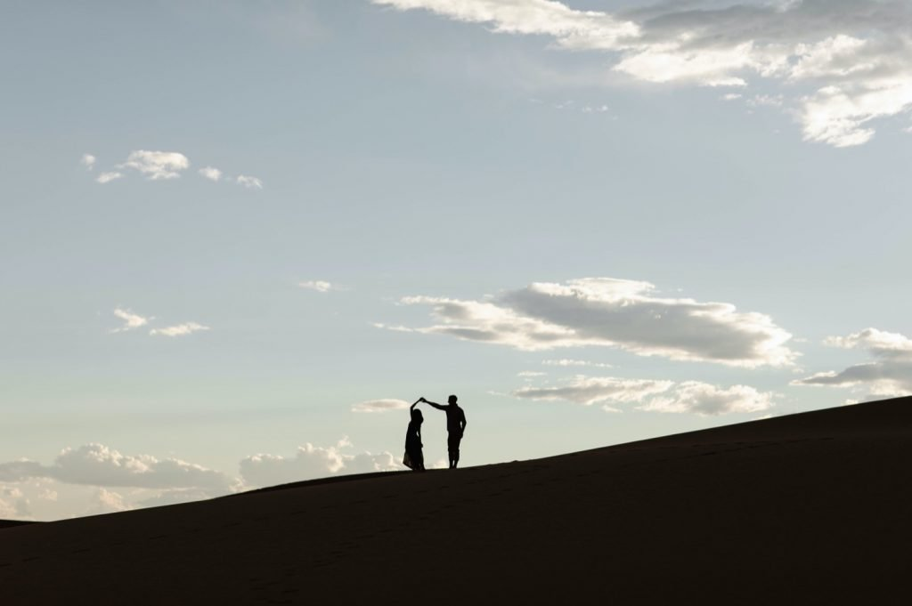 silhouette of a couple during their sand dunes engagement photos