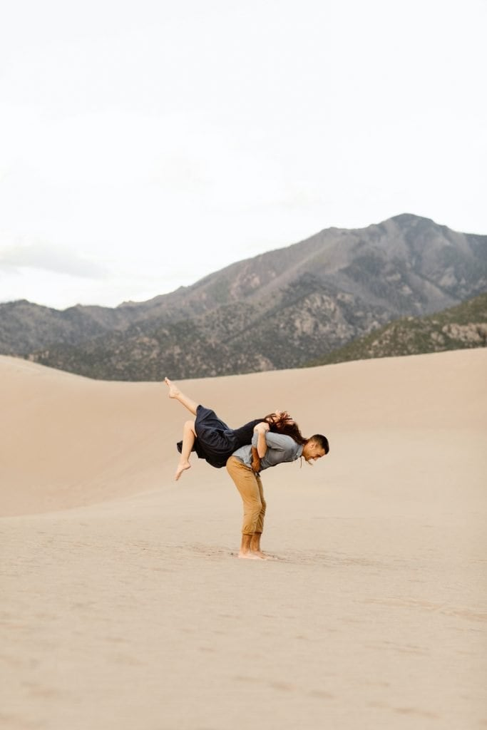 guy lifting girl on his back at the sand dunes with mountains in the background
