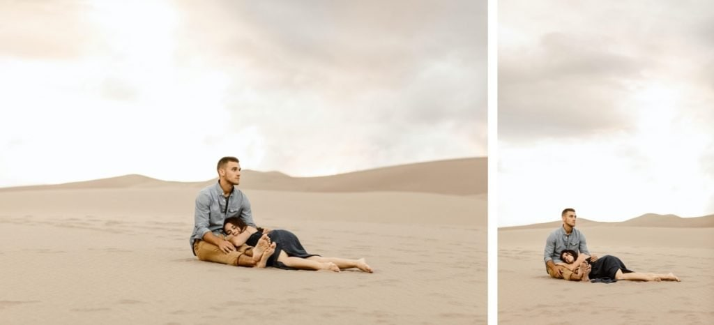 couple sitting on the ground during their sand dunes engagement photos