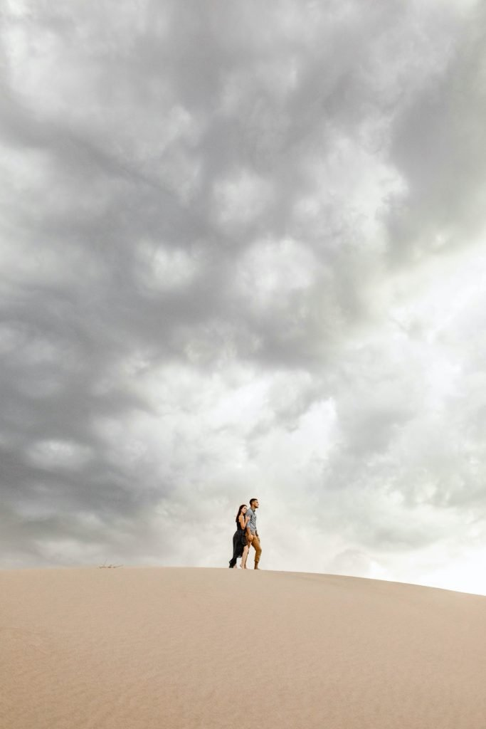 sand dunes engagement photos taken at sunset with giant storm clouds
