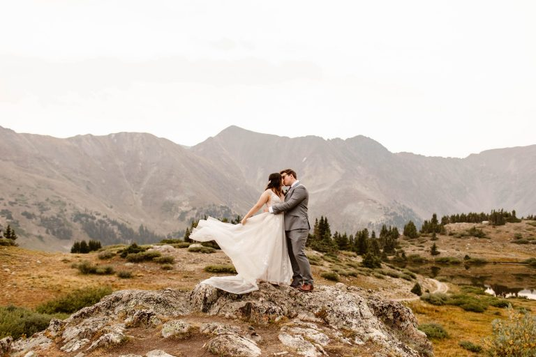 bride tossing her dress in the wind for her sunrise adventure wedding in Keystone photographed by Colorado elopement photographers