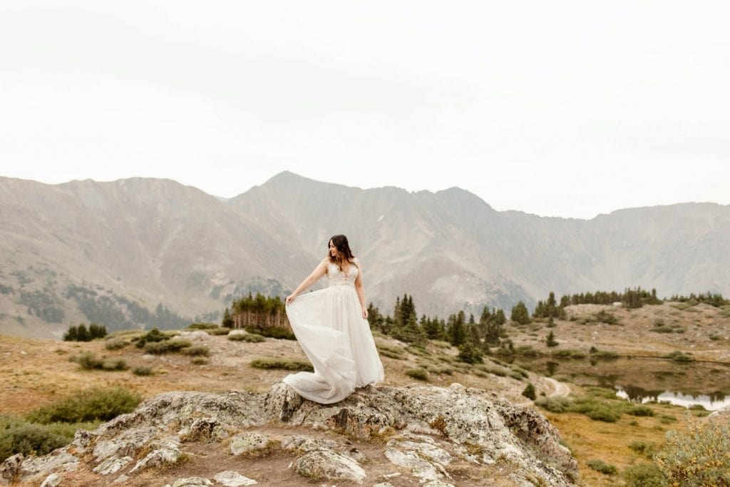 bride in the mountains before her sunrise elopement