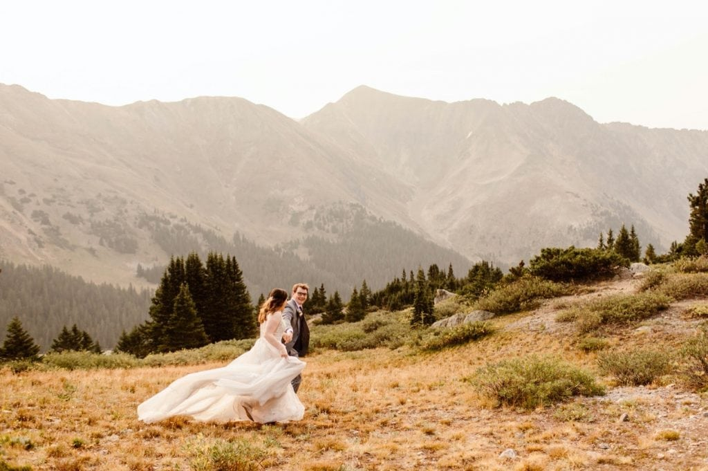 couple walking down a hiking trail together during their elopement