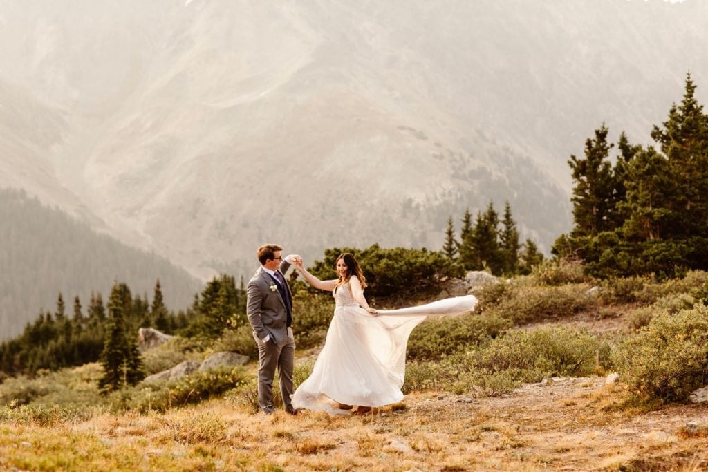 eloping couple dancing in the mountains