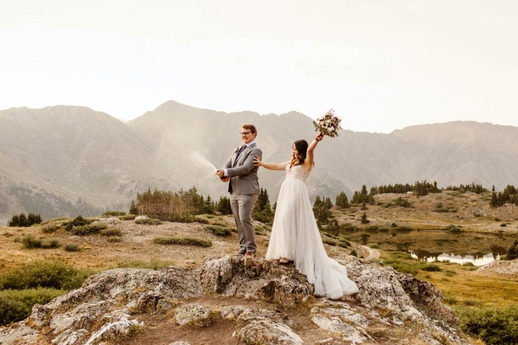 couple popping champagne during their sunrise elopement near Keystone