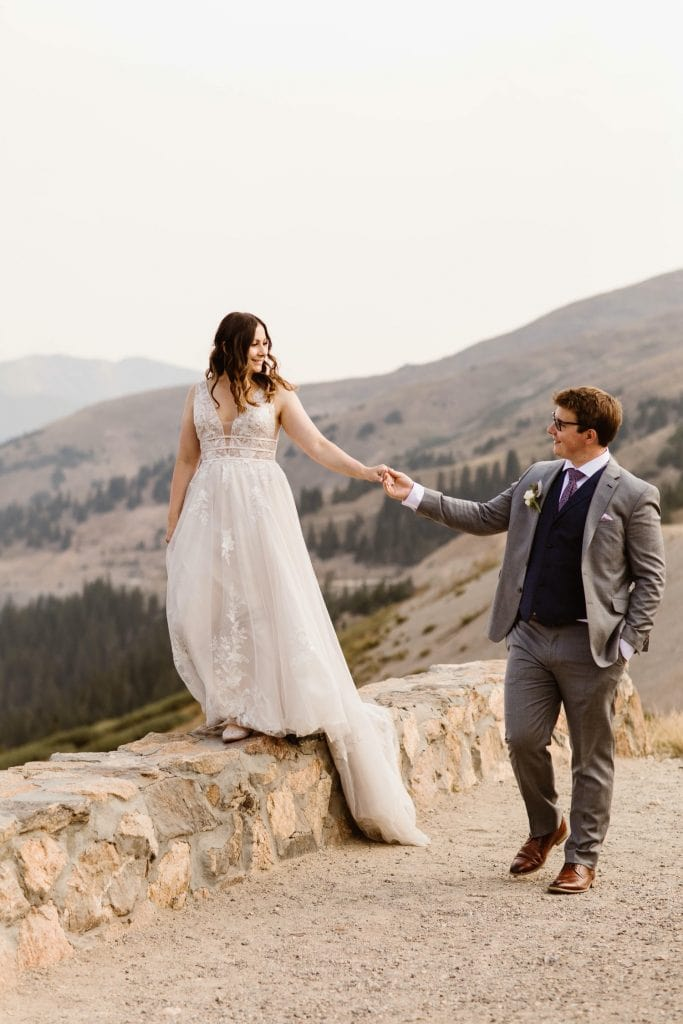 bride and groom looking out onto the hazy Rocky Mountains after their sunrise elopement