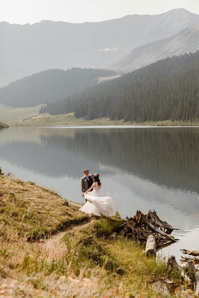 couple dancing lakeside after they eloped at sunrise
