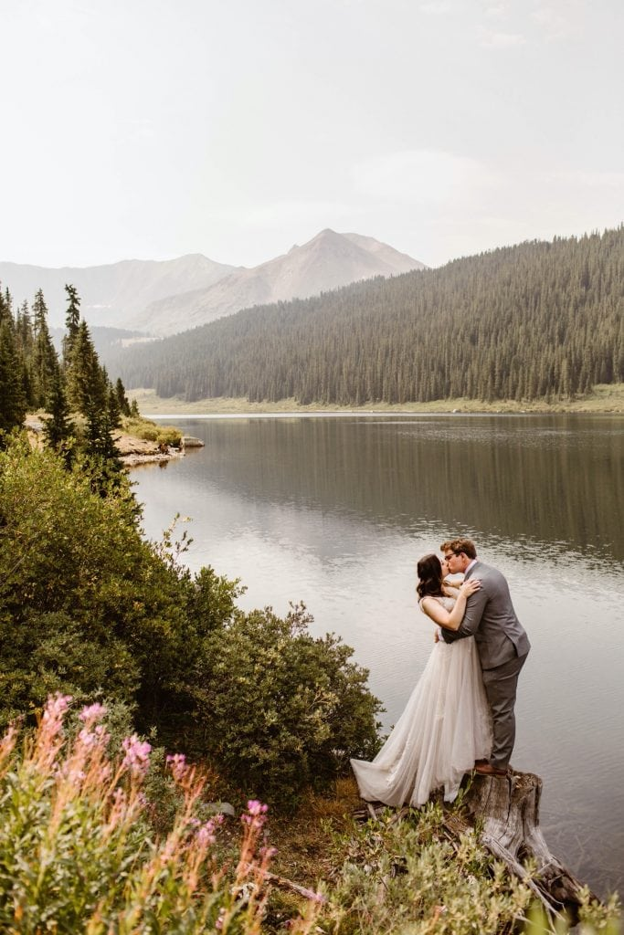 couple standing by a lake near Breckenridge after they eloped at sunrise