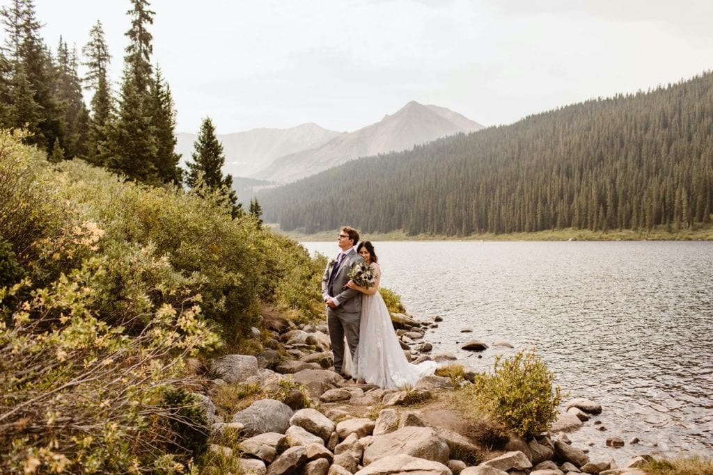 sunrise elopement photos of a bride snuggling up to the groom's back