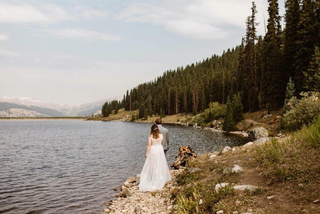 eloping couple walking alongside an alpine lake