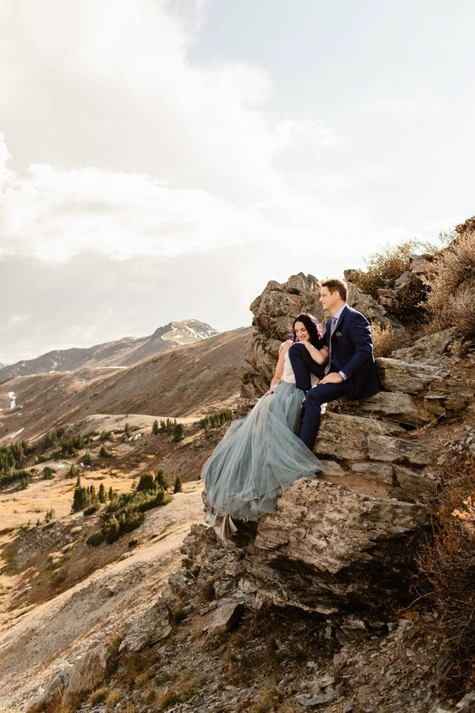 bride and groom sitting together on a cliffside as the wind blows by on their Buena Vista elopement day