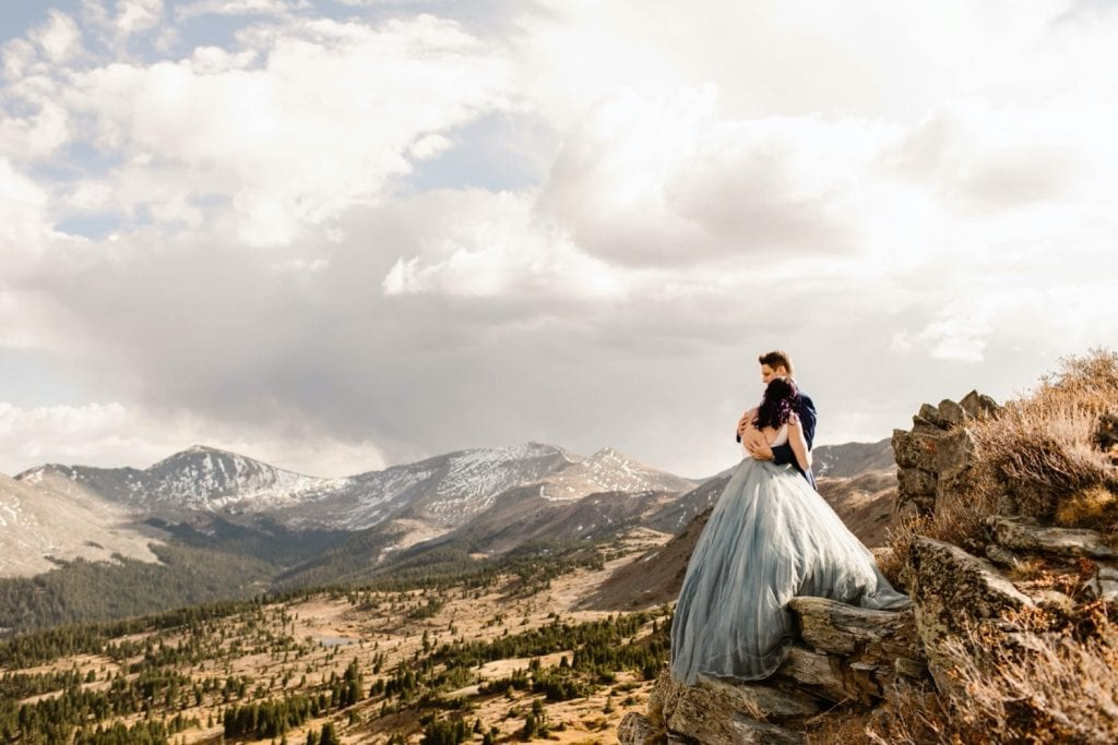 bride and groom hugging each other on the edge of a cliff on their elopement day in Buena Vista Colorado