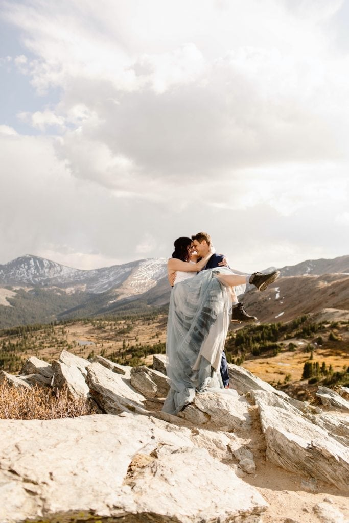 groom lifting bride and spinning her around on the top of a mountain in Buena Vista Colorado