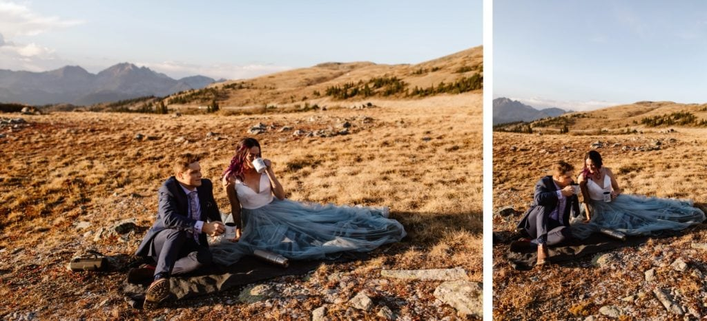 eloping couple drinking hot cocoa while sitting on a picnic blanket in the mountains