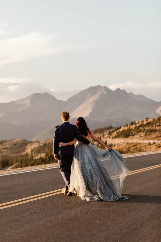 bride and groom walking down a mountain road at sunset near their Buena Vista elopement location