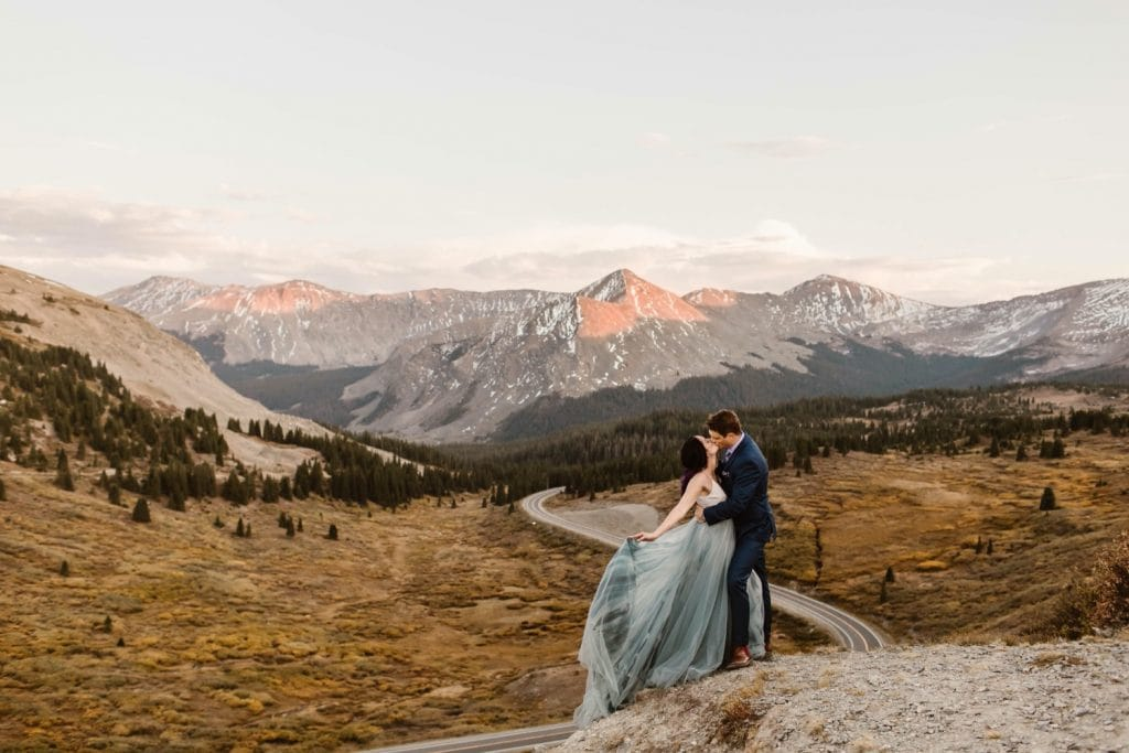 Buena Vista elopement couple kissing on the edge of a cliff overlooking a giant switchback curve in the road