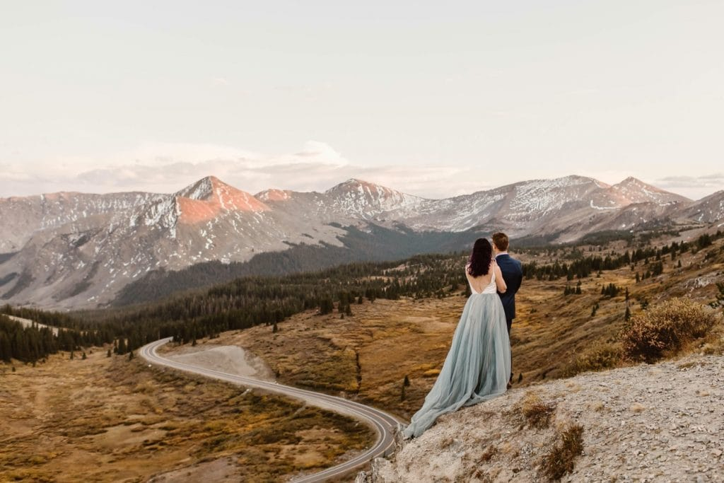 Buena Vista elopement couple standing on the edge of a cliff overlooking a giant switchback curve in the road