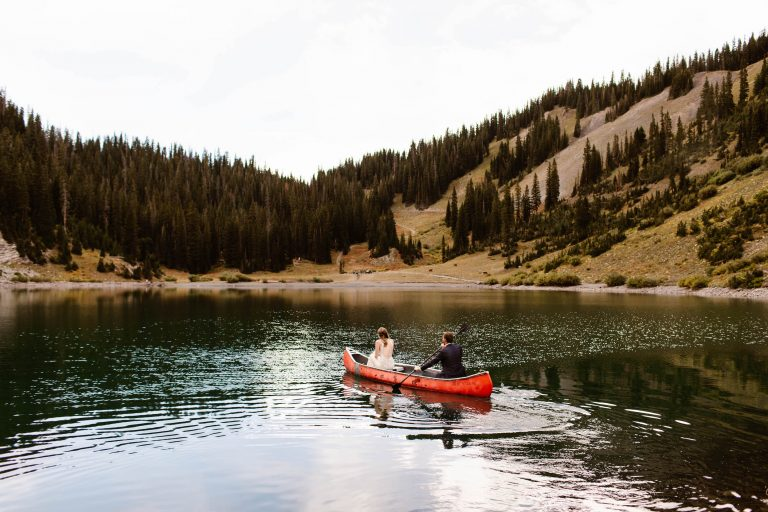 couple canoeing on an alpine lake while being photographed by a Colorado adventure elopement photographer