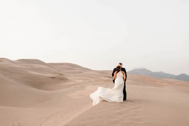 couple kissing on a sand dune while being photographed by a Colorado adventure elopement photographer