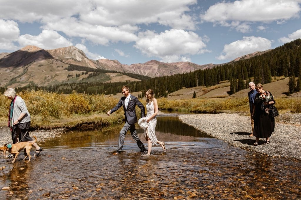 eloping couple wading in the water of the East River in Crested Butte