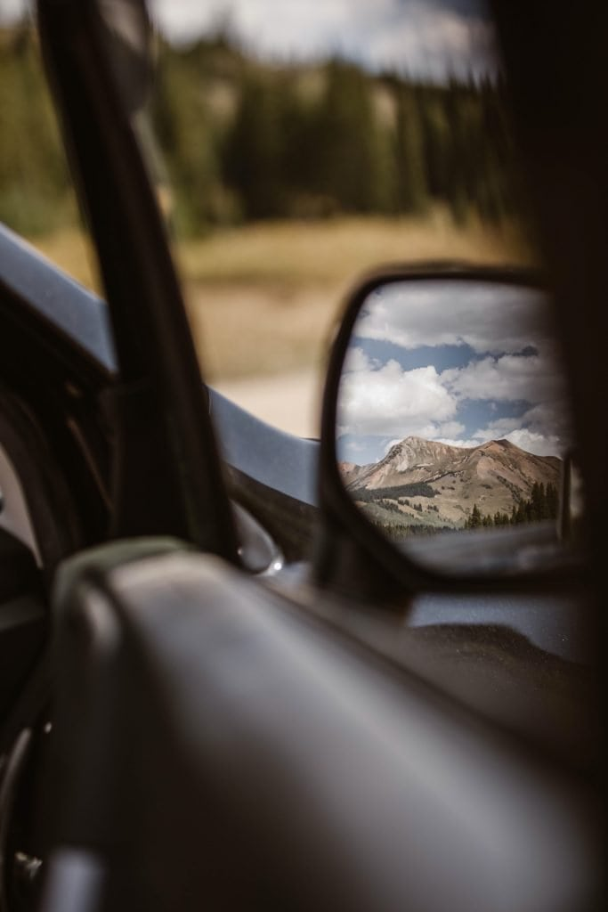 view of the mountains in Crested Butte from the side view mirror of the car