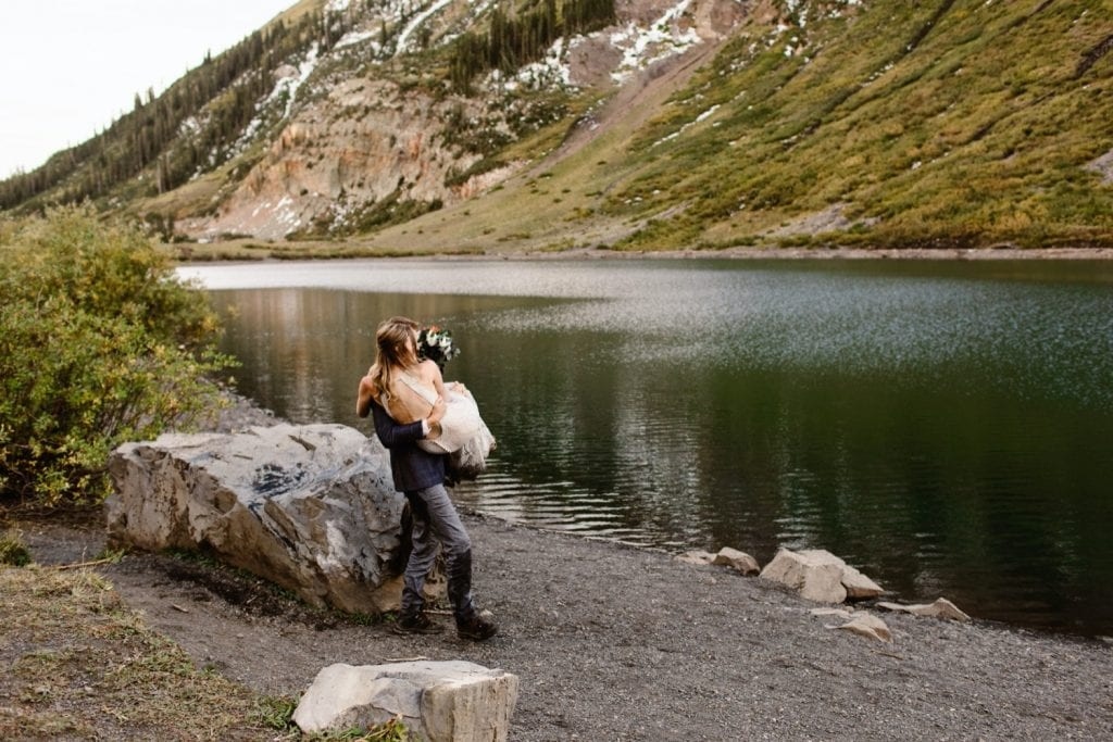 groom carrying bride alongside the shore of a lake near Crested Butte