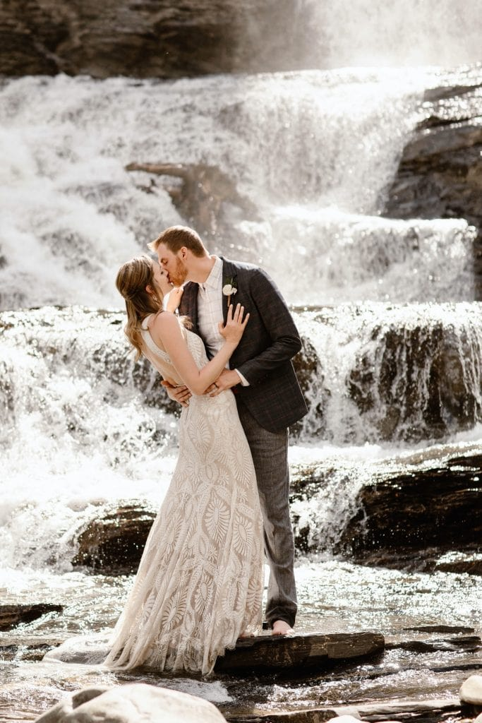 Crested Butte waterfall elopement photo of a newly married couple kissing
